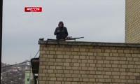 Мужчина с винтовкой на крыше дома