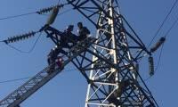 Спасатели поднимаются к мужчине, сидящему на опоре ЛЭП