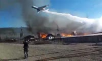 Самолет сбрасывает воду на горящий завод под Кодинском
